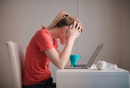 Отчаяна жена с червена блуза стои вкъщи пред лаптопа у дома